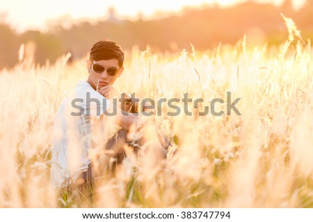 Young man in a meadow at dawn - stock photo