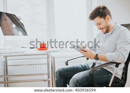 Young man in a modern bright office on sunny day sketching construction project on a tablet and drink coffee - stock photo