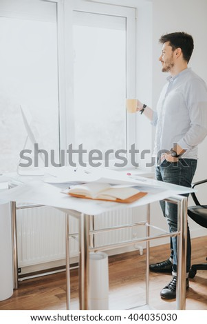 Young man in a modern office design sketching construction project design in a note book computer and drinks coffee - stock photo