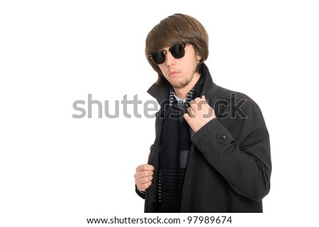Young man in a raincoat and sunglasses - stock photo