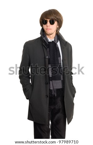 Young man in a raincoat looking to the side. - stock photo