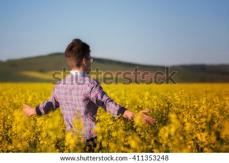 young man in a rapeseed field. Young and joyful. Low key, dark background, spot lighting, and rich Old Masters - stock photo