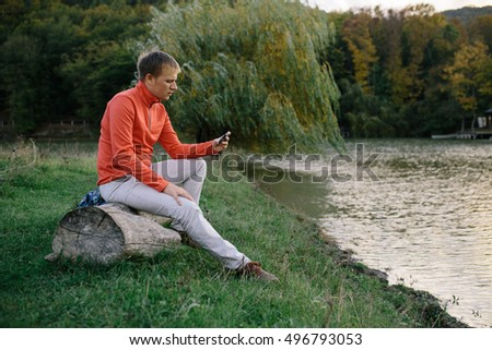 young man in a red sweater relaxing outdoors near lake and uses a mobile phone