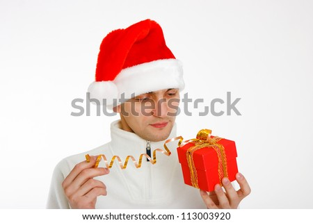 young man in a Santa hat holding a red Christmas gift