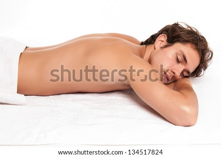 young man in a spa laying down. studio shot isolated on white. - stock photo