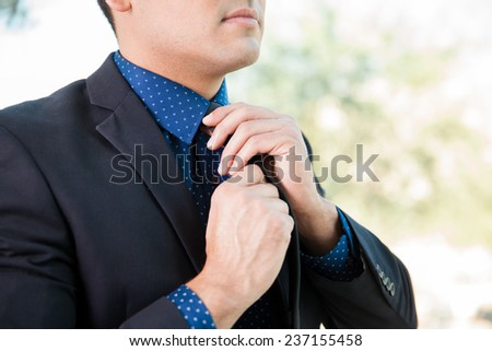 Young man in a suit fixing his tie before attending a job interview - stock photo