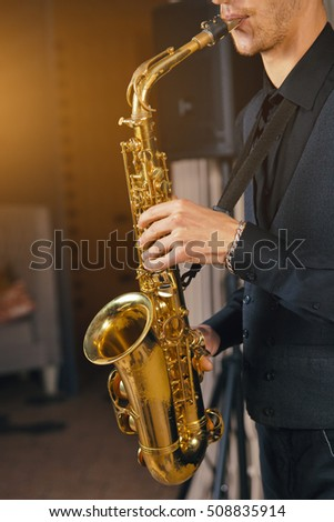 Young man in a suit hold a saxophone musical instrument. Musician, saxophonist plays the saxophone music. Elegant saxophonist plays jazz. Musical instrument saxophone for play music jazz