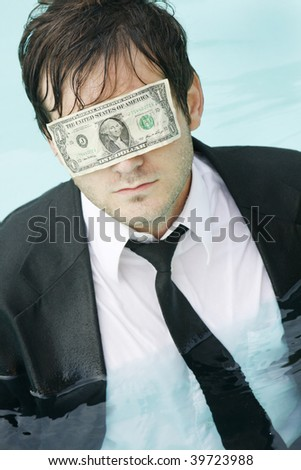 Young man in a suit, in the water, with a dollar bill covering her eyes.