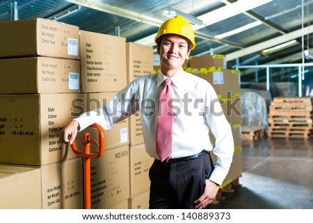 Young man in a suit standing besides boxes and packages in a warehouse