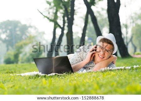 young man in a summer park on the grass with cell phone