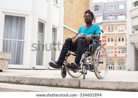 young man in a wheelchair at the top of steps - stock photo