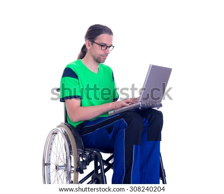 young man in a wheelchair in front of white background with computer - stock photo