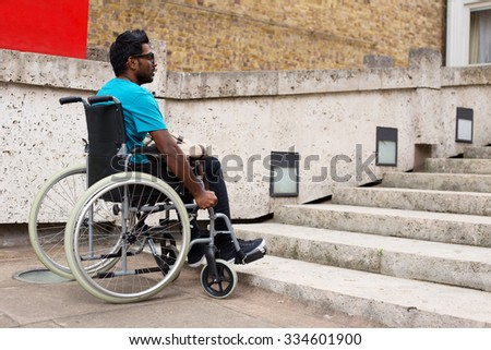 young man in a wheelchair waiting at the bottom of steps - stock photo
