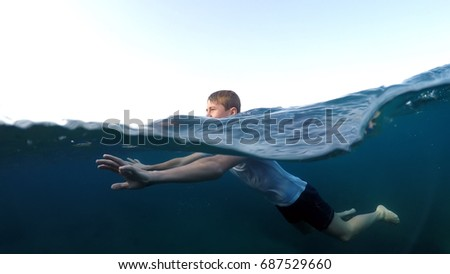 young man in a white shirt is swimming on the sea