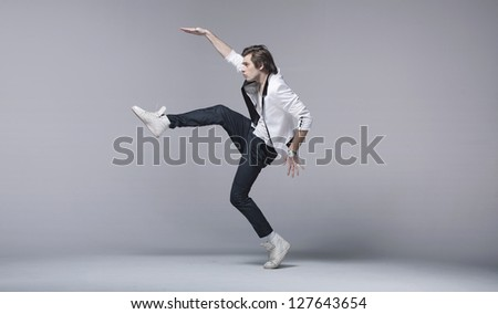 Young man in a white suit as break dancer - stock photo