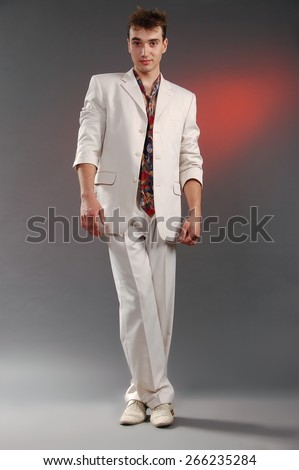 Young man in a white suit posing on gray-pink background - stock photo