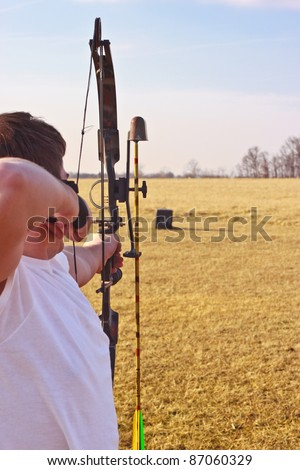 Young man in a white t-shirt aiming loaded bow at target in field - stock photo