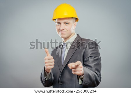 young man in a yellow hard hat showing thumb up - stock photo