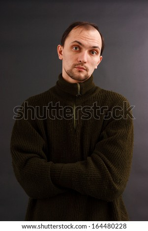 young man in an old sweater on a dark background. studio portrait