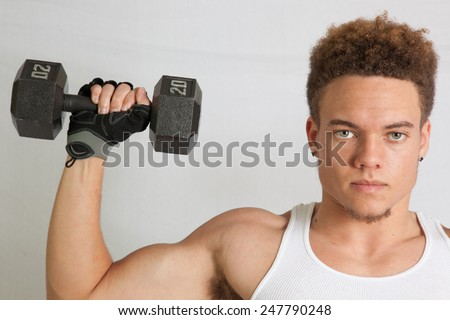 Young man in an undershirt, working out with dumb bells - stock photo