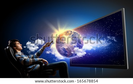 Young man in armchair with click watching TV - stock photo