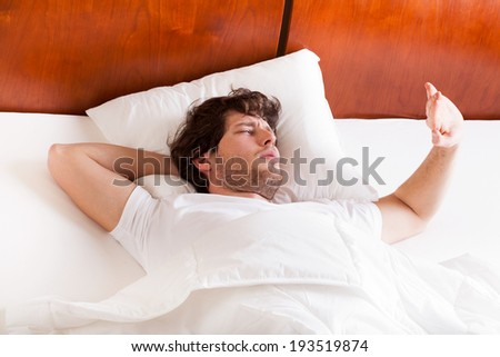 Young man in bed awakened by the sunlight
