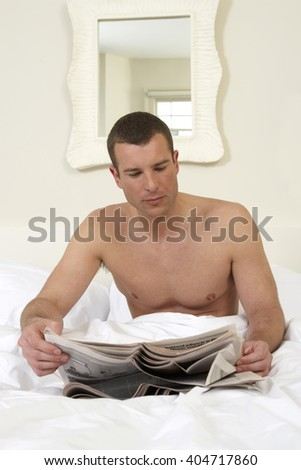 Young man in bed, reading papers - stock photo