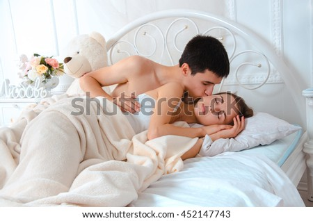 young man in bed with his girlfriend kisses her at the morning