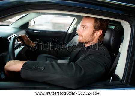 Young man in black driving luxury car, smiling. - stock photo