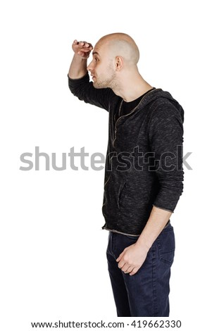 young man in black looking away while keeping his hand over his eyes to protect himself from the sun rays. emotions and people concept. image on a black studio background.