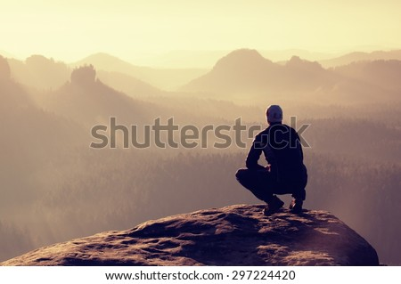 Young man in black sportswear is sitting on cliff's edge and looking to misty valley bellow - stock photo