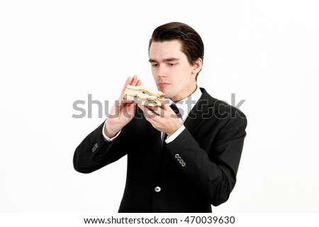 Young man in black suit eating sandwich against white background