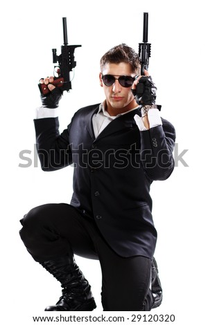 young man in black suit holding gun isolated on white