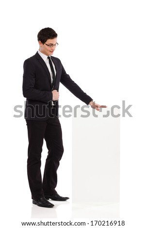 Young man in black suit looking at the banner. Full length studio shot isolated on white. - stock photo