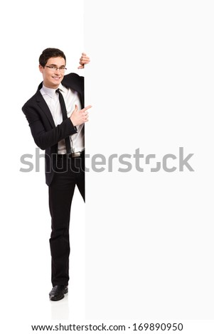 Young man in black suit pointing at the banner. Full length studio shot isolated on white.