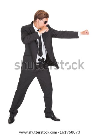 Young Man In Black Suit Punching On White Background