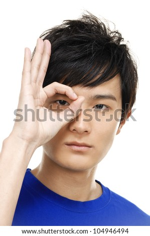 Young man in black t-shirt is showing sign ok on eye