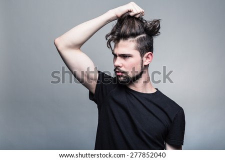 Young man in  black T-shirt with fashionable hairstyle - stock photo