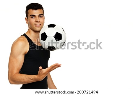 Young man in black undershirt playing with soccer ball, with space for text - stock photo