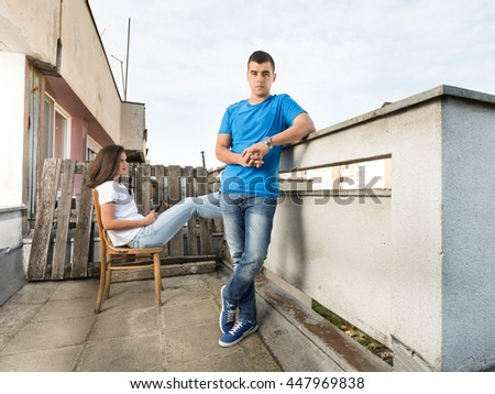 Young man in blue shirt and young woman enjoying on rooftop terrace