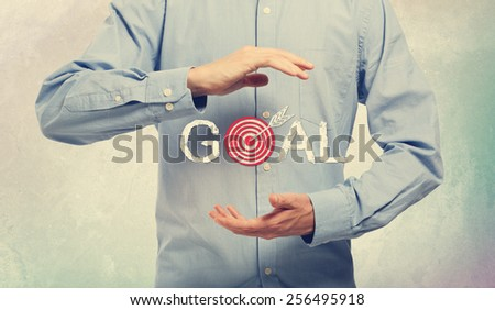 Young man in blue shirt holding a concept of goal - stock photo