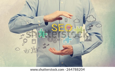 Young man in blue shirt holding SEO concepts - stock photo
