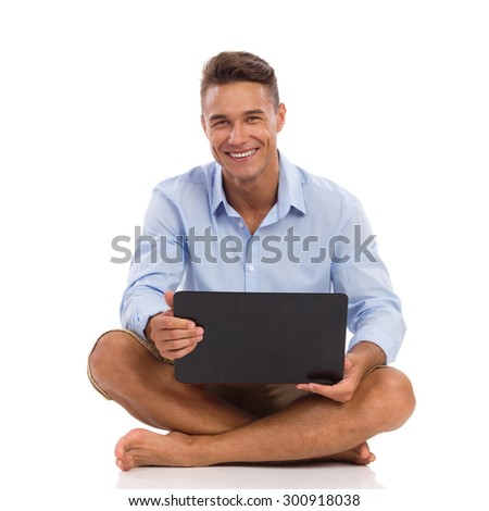 Young man in blue shirt holds laptop on his crossed legs and smiling. Full length studio shot isolated on white. - stock photo