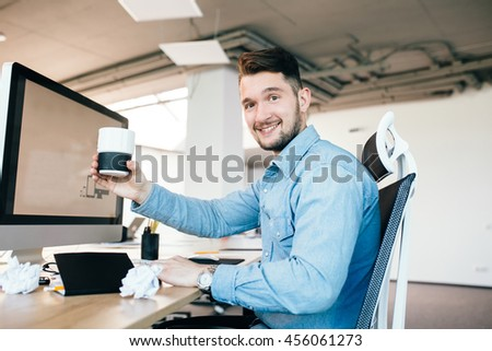 Young man in blue shirt is sitting at his workplace in office. He wears blue shirt.  He holds a cup and smiles to the camera.