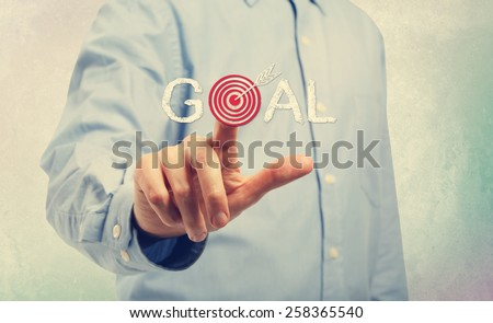 Young man in blue shirt pointing at Goal concepts - stock photo