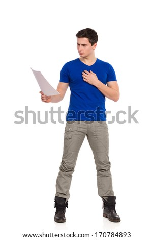 Young man in blue shirt reading document. Full length studio shot isolated on white.