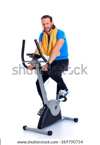 young man in blue shirt train with fitness machine and listening music - stock photo