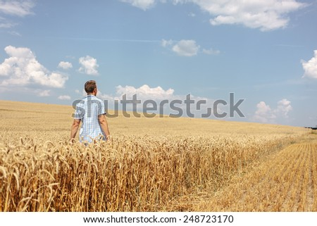 Young man in blue shirt walking in the field