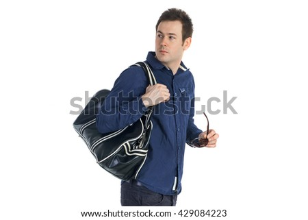 Young man in blue shirt with leather bag holding sunglasses and looking back