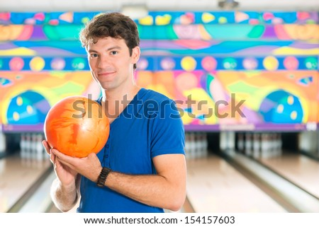Young man in bowling alley having fun, the sporty man holding a bowling ball in front of the ten pin alley